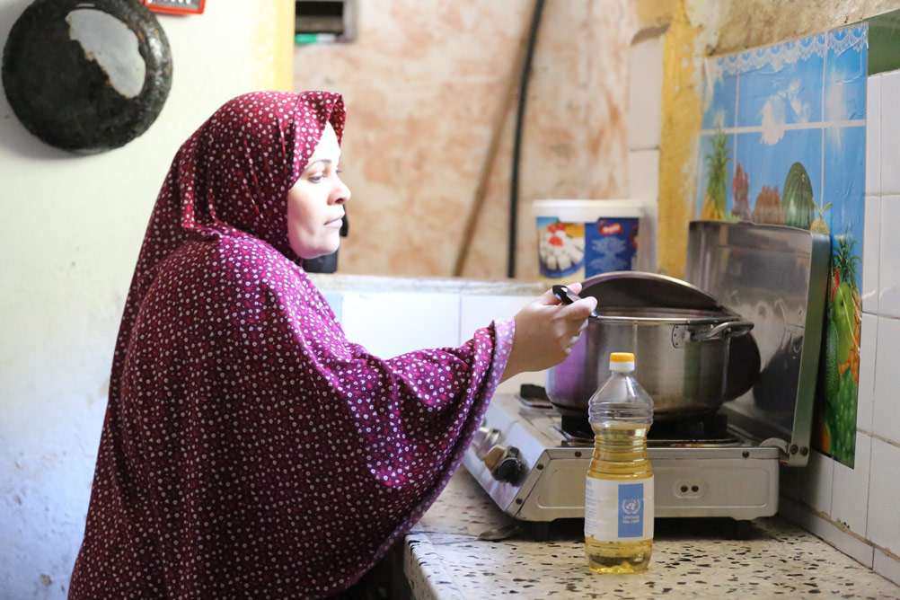 Ayesha El Sabti cooks a meal for her family using the content of a food parcel she receives from UNRWA periodically, Gaza Strip. © 2015 UNRWA Photo by Tamer Hamam