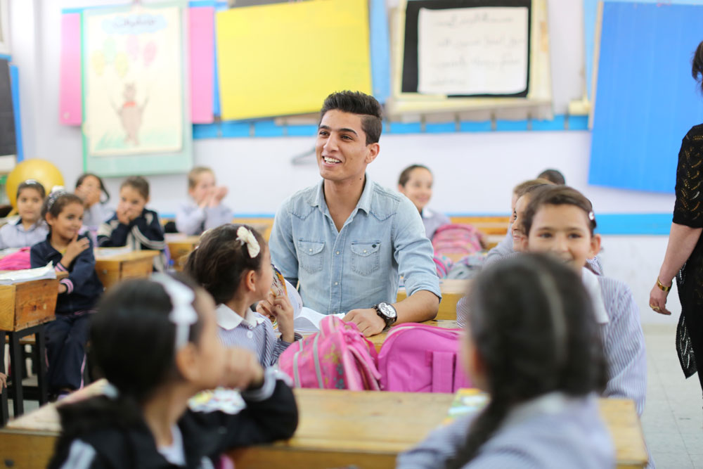 """UNRWA Regional Youth Ambassador Mohammed Assaf visiting students at an UNRWA girls' school in the Palestine refugee camp of Am'ari, near Ramallah. © 2013 UNRWA Photo by Alaa Ghosheh"