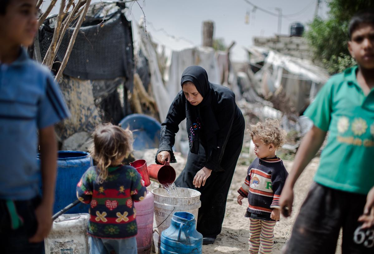 """""""Às vezes, nós ficamos muitos dias sem poder lavar as roupas. As crianças pegam sarna e piolho"""", conta Salwa, que vive com sua família em um abrigo improvisado em Khan Younis, sul de Gaza. A casa de Salwa, como a da maioria das pessoas em Gaza, não está conectada à rede municipal de água. Foto: Tamer Hamam/ UNRWA"""