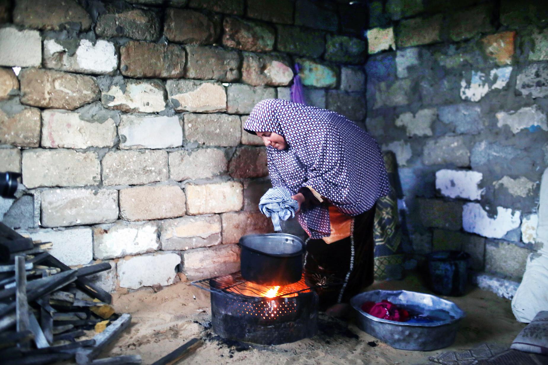 على غرار الكثيرين في غزة، تستخدم لاجئة فلسطينيية في مخيم الشاطئ للاجئين، غرب مدينة غزة، الوسيلة الوحيدة المتاحة لها لطهي الطعام وغسل الملابس ©2017 الأونروا، تصوير: تامر حمام