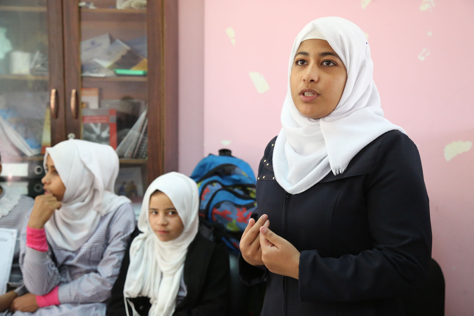 """Maha Abu Singir, a student from al-Maghazi Girls' Secondary School, engages in a discussion with a lawyer from the legal unit at al-Maghazi WPC during the activities held for the 16 days campaign. """"I came here today because I wanted to know more about this campaign, about my rights. I wanted to continue my education because I know that it is my power. I wanted to be a source of pride for my family and for my community as well,"""" Maha commented confidently. """"I know that being deprived of a good education will result in being deprived of many other things; therefore, education is very important to women in my community,"""" she added. © 2015 UNRWA Photo by Tamer Hamam"""