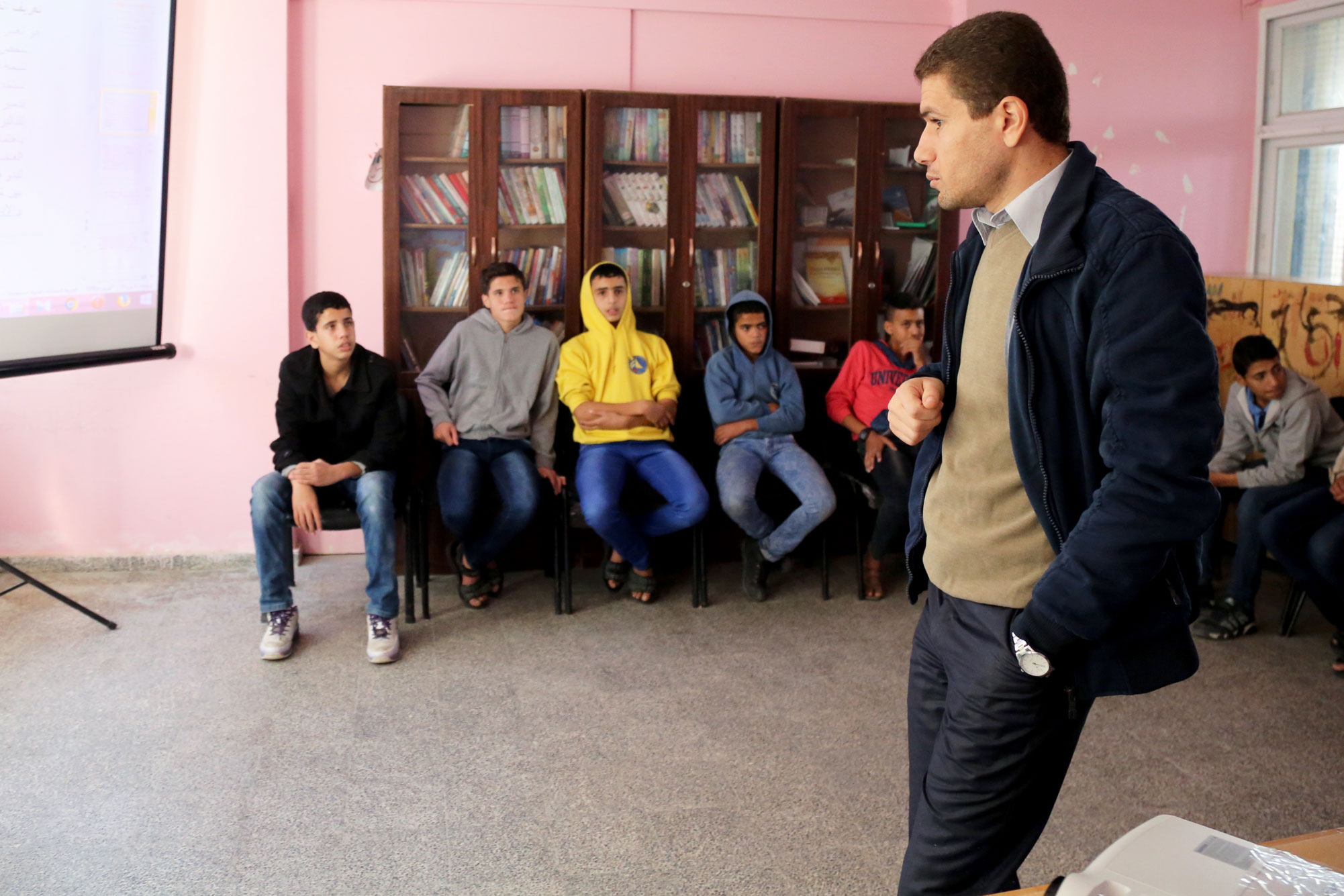 "Ayman Abu Musabeh, a lawyer from the legal unit at al-Maghazi WPC, explains to a group of male students the aim of this campaign and why it is so important. ""Our target is preparatory schools students. We gave them the chance to see things differently, and then they spread the knowledge they gain through these awareness sessions,"" said Mr. Musabeh. © 2015 UNRWA Photo by Tamer Hamam"