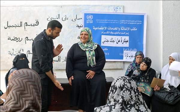 Um Mohammed carefully pays attention to the physiotherapist advice during an UNRWA healthy life awareness session, August 2015. © 2015 UNRWA Photo by Tamer Hamam