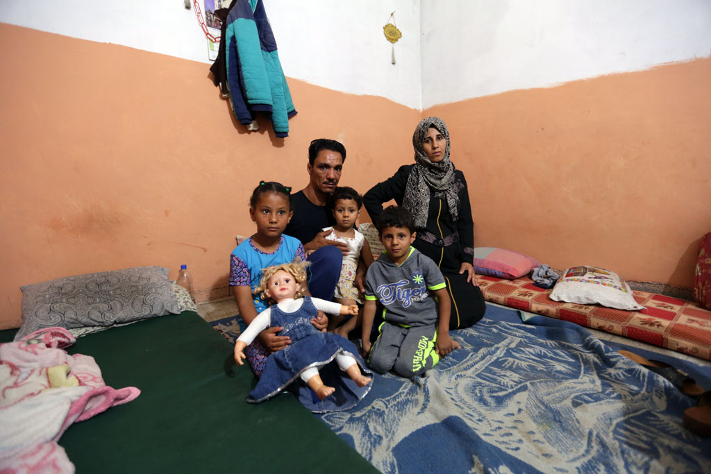 Mohammad Mahmoud Abu Harb and his family sitting on the floor of the only room in their make-shift shelter in Beach camp, western Gaza city. © 2016 UNRWA Photo by Hussein Jaber