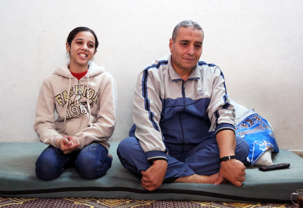 Abdel Kareem Al Ijleh and his daughter Zein in their rented apartment in Gaza city. © 2015 UNRWA Photo by Tamer Hamam