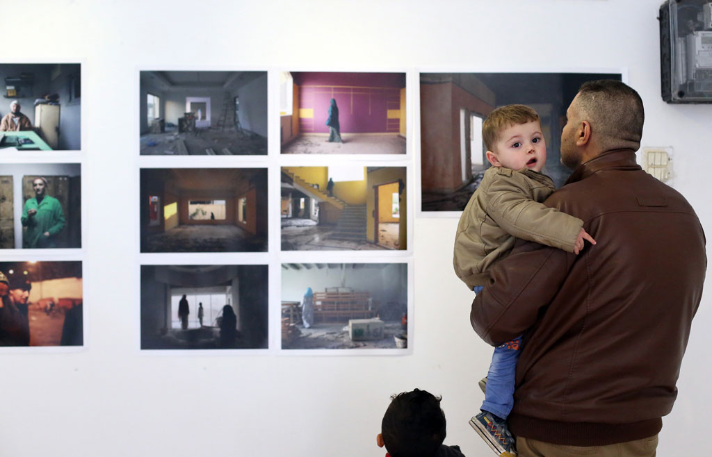 A man and his sons are enjoying the 'Next to Here' photo exhibition, which opened on 16 March in the Shababeek ('windows') art gallery in Gaza City. © 2016 UNRWA Photo by Tamer Hamam