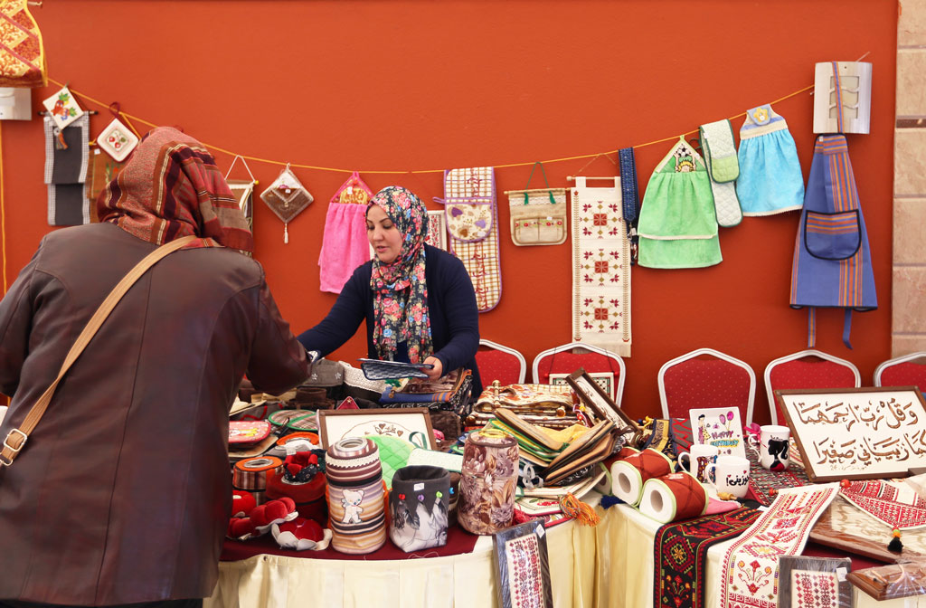 Shireen al-Rayyes is selling her handmade embroidery products in the Lighthouse restaurant in Gaza City. © 2016 UNRWA Photo by Tamer Hamam