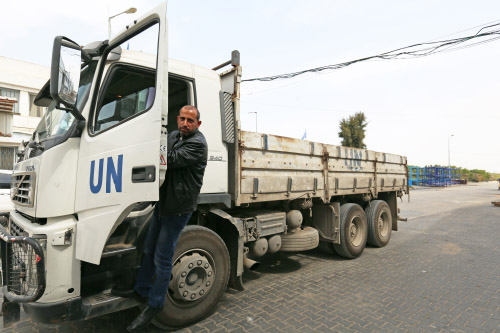 Fares Ramadan Auda is stepping down from his truck at Karni industrial zone east of Gaza city in eastern Gaza; the father of six children has been employed as truck driver at UNRWA for three years and is proud of his work. © 2016 UNRWA Photo by Tamer Hamam