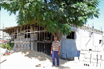 Husam Al Ghoula, standing in front of the house that he is currently reconstructing, August 2015. Photo credit: ©UNRWA Gaza 2015. Photo by Tamer  Hamam.