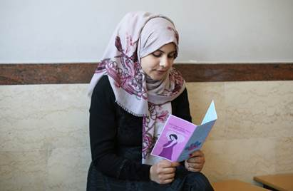 25-year old Palestine refugee Nihaya Al Qidra is reading a brochure on the importance of early registration of pregnancy in the waiting area in the UNWRA Khan Younis Health Centre in southern Gaza. © 2016 UNRWA Photo by Tamer Abu Hamam