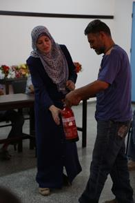 Nadeen Salem is training an UNRWA guard on the use of fire extinguishers during a Safety and Security Division training session in the Khan Younis Training Centre in southern Gaza. Gaza Photo credit: ©UNRWA Gaza 2016. Photo by Mohammad. Yaghi.