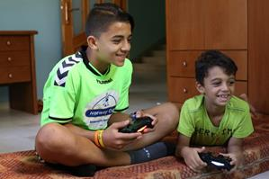Kamal Al Deen Hijo (left) and his brother while playing football on their play station in their home in Al Zahra, Gaza Middle Area. © 2016 UNRWA Photo by Tamer Hamam