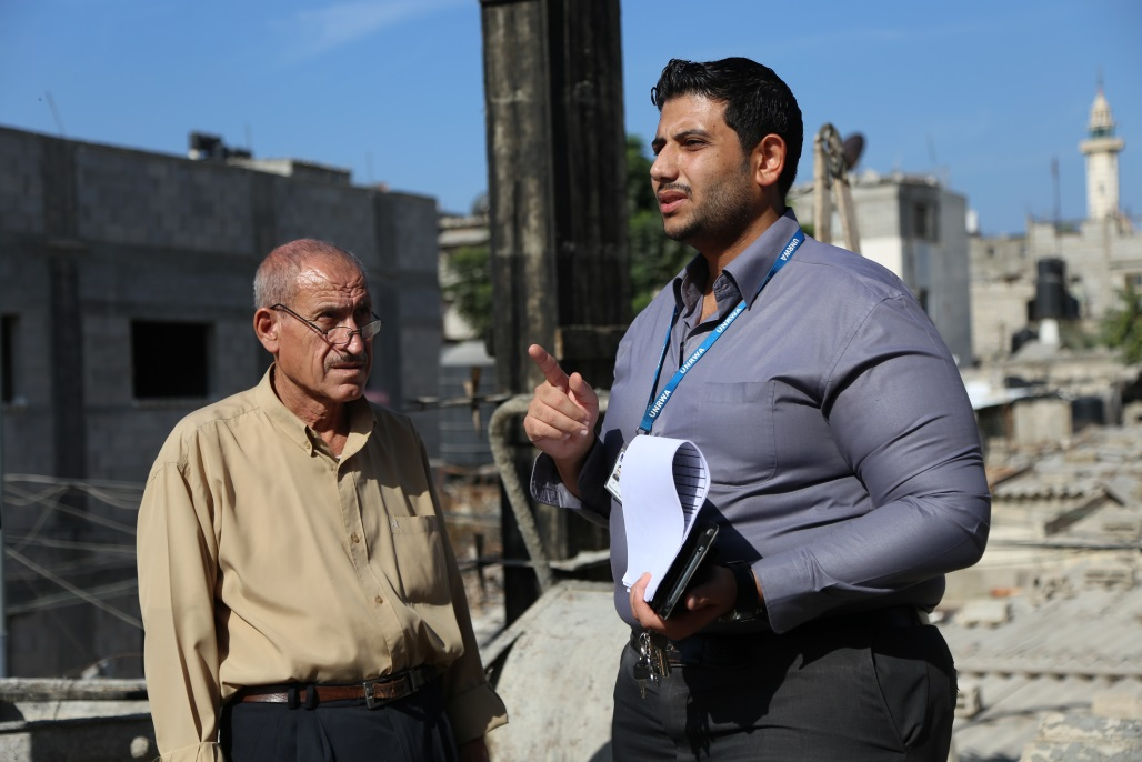 Abdallah Ghazal (right) is following up on the reconstruction progress of Mohammed Saleh's home in Jabalia camp, northern Gaza. © 2016 UNRWA Photo by Mohmmed Al-Hinnawi