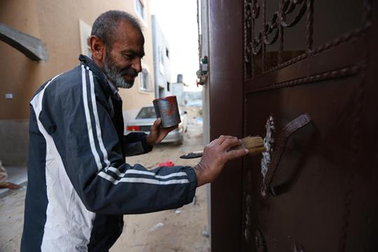 Shukri Ali is painting the door of his house which was totally destroyed during the 2014 conflict and was recently reconstructed with the help of UNRWA in Gaza. Photo credit: ©UNRWA Gaza 2016. Photo by Rushdi Al-Sarraj.