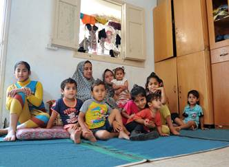 Rima Fadel Al Masri is sitting on the floor of her newly rented house, surrounded by her ten children. Photo credit: © UNRWA 2015. Photo by Ahmad Awad