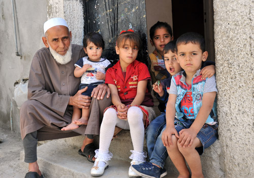 73-year old Khalil Hassan Sorour with his grandchildren in front of their house in Jabalia,  Gaza. © 2015 UNRWA Photo by Khalil Adwan