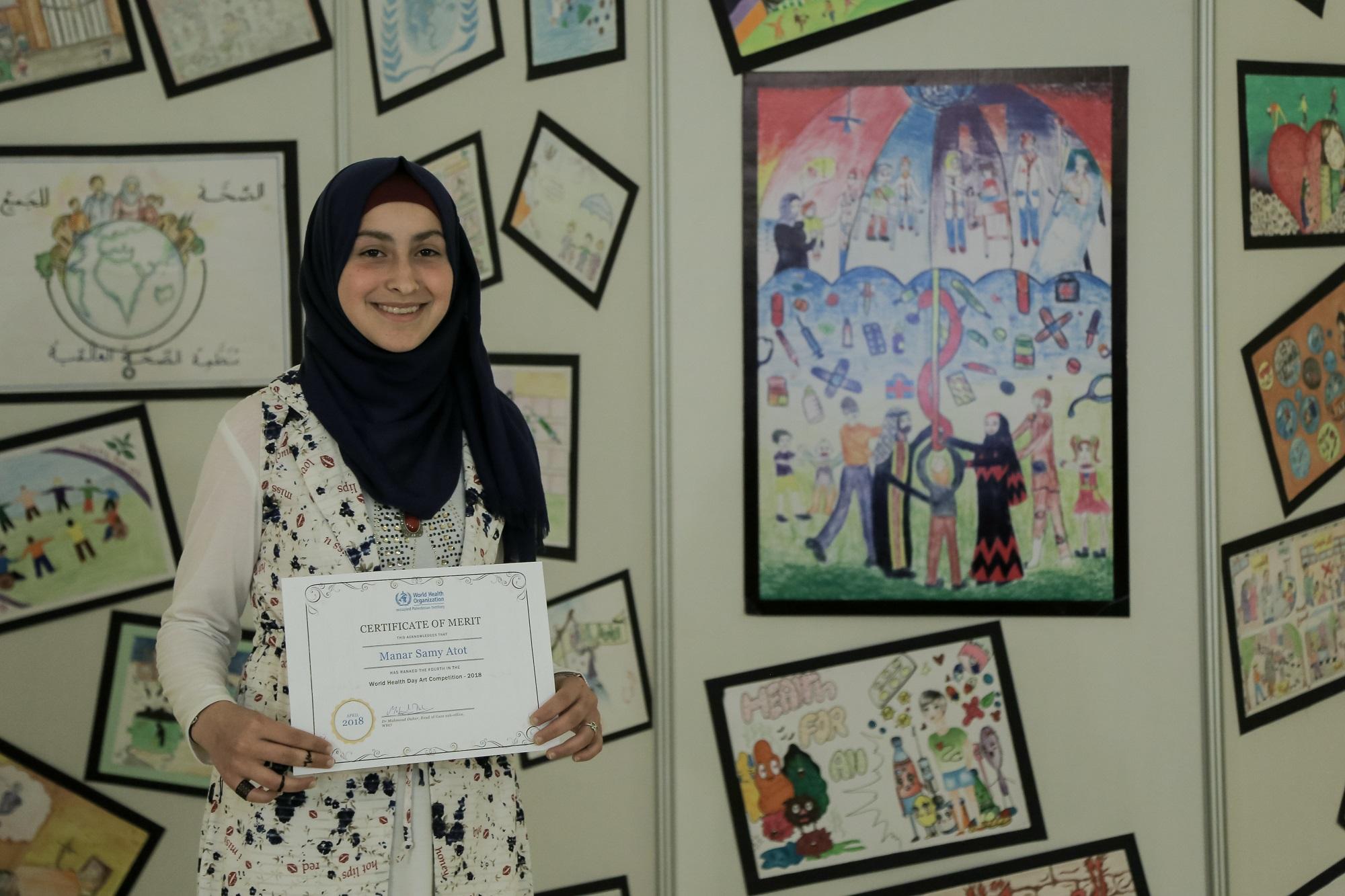 """منار سامي عطوط، 14 عام، طالبة في مدرسة رفح الإعدادية للبنات """"د""""، تحمل شهادة الاستحقاق وإلى جانبها لوحتها الفائزة خلال الحفل الختامي لمسابقة الرسم المنظمة من قبل منظمة الصحة العالمية الذي نظم في مركز رشاد الشوا في مدينة غزة. جميع الحقوق محفوظة: الأونروا غز"""
