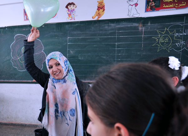 """Humans have a stronger capacity than we realise,"" says counsellor Khitam Qatamesh, seen here working with children in an UNRWA school in Gaza City. Khitam helps children to better cope with the extreme challenges they face on a daily basis. © 2015 UNRWA"