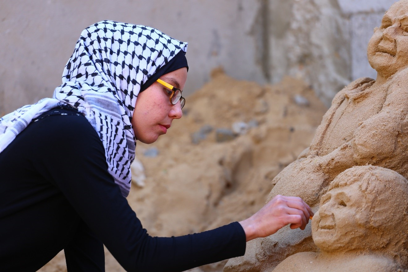 Ranna Al Rimlawi 24 years-old passionately works on one of her sand sculptures at her home in Gaza City, Gaza. © 2019 UNRWA Photo by Ibrahim Abu Usheeba