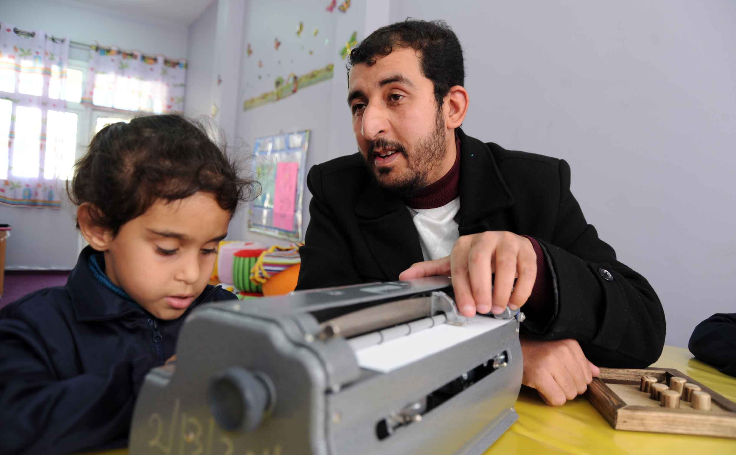 Mohamed Abu Mousa is teaching 4 year-old Salma how to use type the Arabic alphabet in Braille language. Mohamed was once himself a pupil at RCVI.