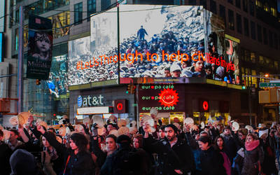 """A supporter holds pita bread in front of the projected iconic image of the Yarmouk crisis in Syria at the Syria flash mob held in Times Square. 20 March 2014, New York City, USA. © Smita Sharma/UNRWA Archives"