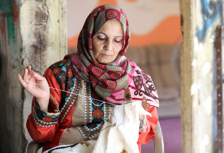 Awated Badr in her house in Deir El Balah doing embroidery work; she joined the UNRWA supported Sulafa Embroidery Centre almost 20 years ago. © UNRWA 2015. Photo by Khalil Adwan