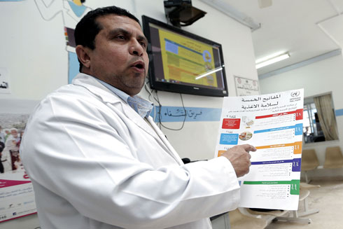 An UNRWA staff member discusses the 'five keys to safer food' at South Baqa'a health centre in Jordan. © UNRWA Photo