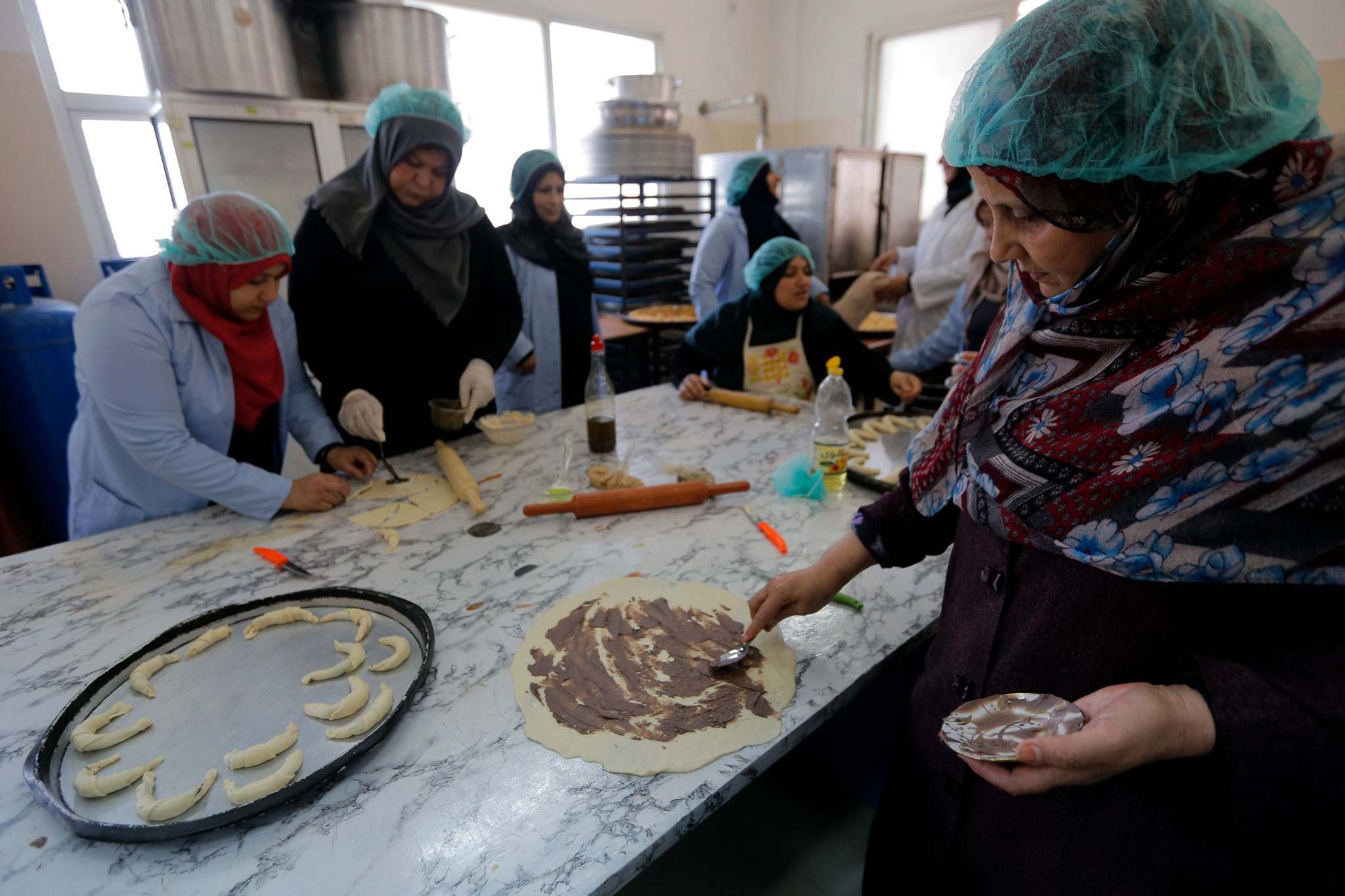 Latifa Al-Mabhouh (right) and other participants in the UNRWA Women Programme Centres (WPCs) food processing training in Jabalia, northern Gaza Strip. © 2017 UNRWA Photo by Rushdi Al-Saraj