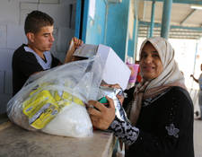 A Palestine refugee woman receives food assistance at the UNRWA Khan Younis Distribution Centre in Gaza. This year's oPt Emergency Appeal will provide emergency food assistance to more than 900,000 Palestine refugees in Gaza to help ensure that their minimum nutritional needs are met. © 2016 UNRWA Photo by Tamer Hamam