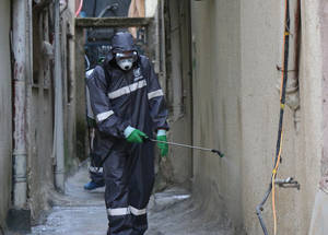 """UNRWA sanitation workers wearing protective health gear in the Aida Refugee Camp perform a sterilization of the camp's streets and buildings. UNRWA has stepped up its sterilization efforts in the 19 refugee camps across the West Bank, performing regular cleanings of the camps streets and UNRWA facilities. Adam Baraqa'a, one of the sanitation workers and a resident of the Beit Jibreen camp, says that while the coronavirus pandemic has been a scary time, """"I feel proud that I can do something to help protect my community, and I feel safe while doing it because of the protective gear that UNRWA has provided us with.""""  © 2020 UNRWA Photo by Yumna Patel"""