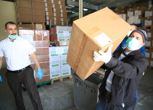 UNRWA staff load medical supplies to be distributed around the West Bank, where 50,000 surgical masks have been distributed to staff in the 43 Health Centers across the territory, including gowns, and personal protective equipment (PPE) for food distribution teams. There is an urgent need for more medical supplies across the five fields of UNRWA operations in order to support strengthened hygiene and cleaning practices at the organization's health centers. UNRWA estimates a need for US$ 3,600,000 in emergency funding in order to supply  the adequate amount of PPE kits, masks, gloves, hygiene items, and cleaning and disinfection materials for its staff. © 2020 UNRWA Photo by Marwan Baghdadi.