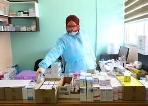 UNRWA staff members organize medicines to be distributed to beneficiaries at the Rafah Preparatory Girls School, Gaza Strip. As part of the Agency's COVID-19 response, the Rafah Preparatory Girls School is one of several schools that has been turned into a temporary health facility for beneficiaries with respiratory illnesses,  in order to separate between them and other groups to minimize any possible chances of spreading the COVID-19 virus. Additionally, UNRWA staff have implemented awareness sessions among the health staff working in the clinics, as well as among beneficiaries, to inform them of the measures that should be taken to minimize the chances of infection. © 2020 UNRWA Photo by Khalil Adwan.