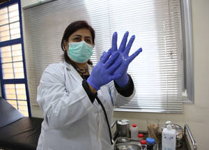 An UNRWA doctor demonstrates hand sanitizing techniques before she performs a check up on beneficiaries at the Damascus Training Centre in Syria. UNRWA has distributed 1-litre hand sanitizer liquid to all 3,500 staff and to volunteers in Syria and ensured it was available to beneficiaries visiting installations. The Agency has also provided personal protective equipment (PPE), medical masks, eye protectors, gowns and gloves to its health workers along with increased cleaning and disinfection of health centres to reduce the risk of transmission for both staff and patients.© 2020 UNRWA Photo by Taghrid Mohammed.