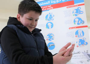 """10-year-old Muaz al-Asadi, sanitizes his hands according to the health guidelines distributed by UNRWA to Palestine refugees at the Damascus Training Centre in Syria. Muaz is a student at UNRWA Haifa school in Damascus. However, as a result of schools being closed to prevent the spread of COVID-19, Muaz is currently studying at home using UNRWA self-learning material.  Muaz says, """"I wash my hands with soap and water and dry them thoroughly to prevent germs from spreading and to keep myself from getting sick. We should make handwashing a habit to avoid coronavirus.  Handwashing minimizes the germs passed around our family and community."""" Currently, all UNRWA schools and TVET centres, which have 541,000 students enrolled, are closed in all fields, in line with host country directives, as are two UNRWA teacher training institutions in the West Bank and Jordan. © 2020 UNRWA Photo by Taghrid Mohammed."""