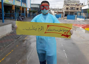 An UNRWA staff member holds up a sign urging people to stay at home, in order to prevent the spread of the coronavirus at the Ma'an Health Centre in Jordan. The practice of social-distancing has been advocated by global health officials as one of the best ways to prevent the spread of a contagious disease like COVID-19. While social-distancing can be difficult to practice in refugee camps that are typically overcrowded and house several families in each apartment, UNRWA has distributed educational pamphlets to Palestine refugees across its five fields of operations teaching beneficiaries how to practice safe social distancing techniques. © 2020 UNRWA Photo