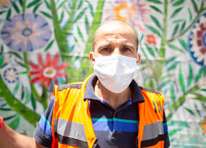"""Mohammad Abu Kishek has been an environmental health laborer in Balata for fifteen years. """"The camp has sixteen main clean-up locations. We see a lot of disposable gloves and facemasks on the ground and have increased our clean-up efforts in response. We usually clean and disinfect the same locations multiple times a day."""" """"Our schedules have changed since the pandemic began. We start our work at six a.m. to three p.m. We also remain on call 24 hours a day, seven days a week. We all had only one day off for Eid! The community needs us and we are here to serve them now, just as we always have."""" """"When I come home from work, my little daughter gleefully shouts, 'Corona! Corona!' and laughs as she runs away,"""" shares Mohammad. """"I'm aware that I am putting myself and my family at risk by being a frontline responder. I make sure to take precautions to protect my family. I shower and change my clothing before I meet with my family after work,"""" said Mohammad. © 2020 UNRWA Photo by Louise Wateridge"""