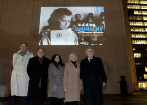 From left H.E. Ambassador Ahmed Fathallah, the Permanent Observer of the Arab League to the UN, Ambassador Feda Abdelhady-Nasser, Deputy Permanent Observer of the State of Palestine to the United Nations, Margot Ellis, UNRWA Deputy Commissioner-General, and H.E. Dr. Riyad H. Mansour, Permanent Observer of the State of Palestine to the United Nations stand in front of an iconic image projected on the UNHQ building, Manhattan, New York City as part of UNRWA's Building Solidarity campaign.