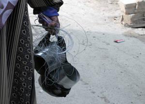 في أشهر الشتاء، غالبا ما تستخدم المعونة النقدية من أجل رفع سوية المساكن. في الصورة امرأة لاجئة فلسطينية وقد قامت بشراء أنابيب للموقد الأساسي، الذي يستخدم للطهي، من السوق في مخيم قبر الست، دمشق. كانون الأول 2014. الحقوق محفوظة للأونروا / تغريد محمد.