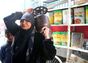Frequent shortages of gas in Syria caused prices to rise rapidly in 2014. No fuel was available in the market on the day this elderly Palestine refugee woman arrived to fill her cooking stove. Qabr Essit camp, December 2014. © UNRWA/Taghrid Mohammad.