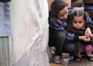 Huddled together, these two girls in sandals try to keep warm. Many Palestine refugees fled their homes in Syria with only the clothes they were wearing. Children who outgrow their clothes and shoes quickly resort to sandals, despite the cold temperatures. Al-Rameh School Collective Shelter, Jaramana camp, Damascus. November 2014. © UNRWA/Taghrid Mohammad.