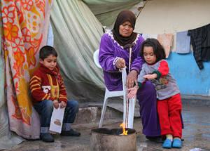 في الوقت الذي يبحثون فيه عن مصدر للتدفئة في الشتاء البارد، فإن هذه المرأة المسنة وأحفادها يمثلون ثلاثة أجيال من لاجئي فلسطين المشردين. إن أكثر من 460,000 لاجئ فلسطيني، يشكلون أكثر من 95% من ما تبقى من السكان اللاجئين، سيكونون بحاجة إلى مساعدة إنسانية مستمرة في عام 2015. الملجأ الجماعي في مدرسة الرامة، مخيم جرمانا، دمشق. تشرين الثاني 2014. الحقوق محفوظة للأونروا / تغريد محمد.