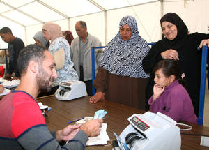 With UK aid support, UNRWA provides 96 per cent of Palestine refugees in Syria with vital cash assistance to meet their humanitarian needs. With the onset of winter, cash assistance is vital in helping families procure adequate clothing, bedding and fuel. Alliance Distribution Centre, Damascus, October 2014. © UNRWA/Tagrid Mohammad.