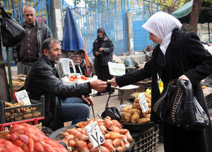 A woman buys fresh vegetables in the street market outside the UNRWA Palestine Institute School for Boys and Girls. December 2014. © UNRWA/Taghrid Mohammad.