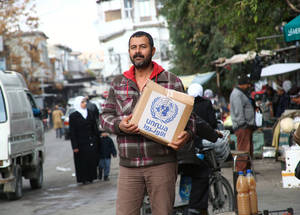 Fresh vegetables supplement the dried goods in UNRWA food parcels. A man holds a box of supplies in Old Damascus, near the UNRWA Alliance Distribution Centre. Each parcel provides 700kcal per person, per day, for one month. December 2014. © UNRWA/Taghrid Mohammad.