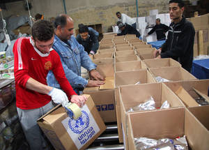 UNRWA provides food parcels to Palestine refugees throughout Syria, assembled in the UNRWA Logistics Compound in Damascus.  Food parcels include staples such as rice, lentils, oil, powdered milk, sugar and canned meat. Damascus, December 2014. © UNRWA/Taghrid Mohammad.