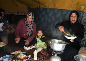 Cash assistance allows Palestine refugee families to keep a balanced diet. A grandmother cooks a traditional vegetable dish for her family, bought at the market outside the Jaramana shelter in Damascus.  Al-Rameh School, Jaramana collective shelter, November 2014. © UNRWA/Taghrid Mohammad.