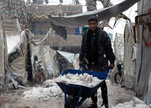 Snow in Damascus is rare and draws families out into the courtyards of collective shelters to witness the weather conditions. Al-Kabri School Collective Shelter, Damascus, 2015. © UNRWA/Taghrid Mohammad.