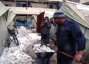 Residents do their best to clear snow from tents before it turns to slush to help open the passages for residents to use. Ara School Collective Shelter, Damascus, 2015. ©UNRWA/Taghrid Mohammad.