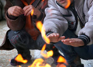 The soaring cost of heating fuel means many Palestine refugees are going cold this winter. These children huddle by a makeshift campfire. Ara School Collective Shelter, Damascus, 2014. © UNRWA/Taghrid Mohammad.