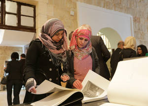 Visitors browse printed photo albums from from the digitized UNRWA Archive. © UNRWA Photo by Alaa Ghosheh